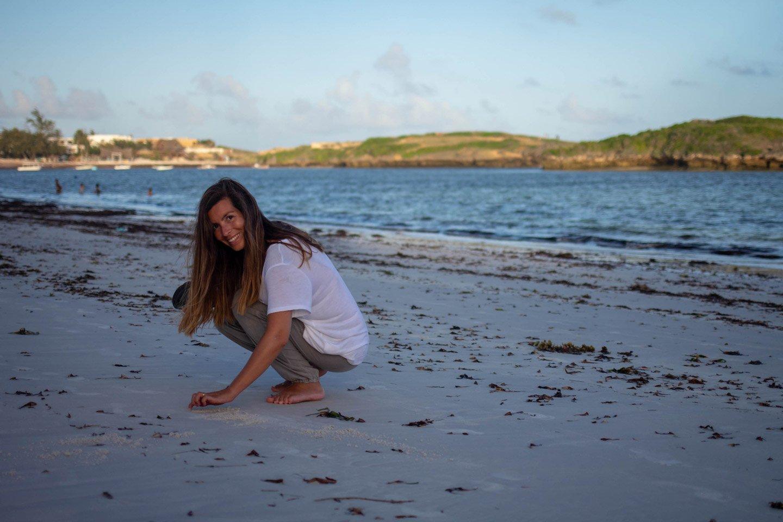 Carla en la playa de Watamu, escribiendo en la arena.